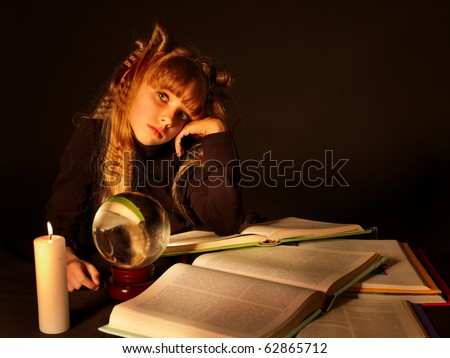 Child reading magic book at candle. Crystal ball on table. - stock photo