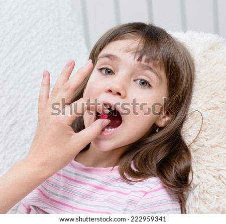 Child receiving pill - closeup - stock photo