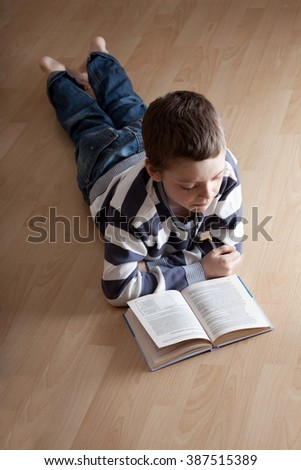 Child reeding book lying on the floor