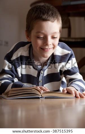 Child reeding book lying on the floor - stock photo