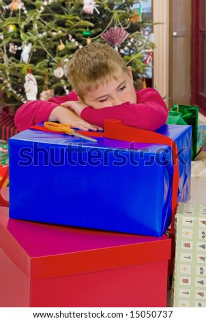 Child resting after wrapping Christmas gifts