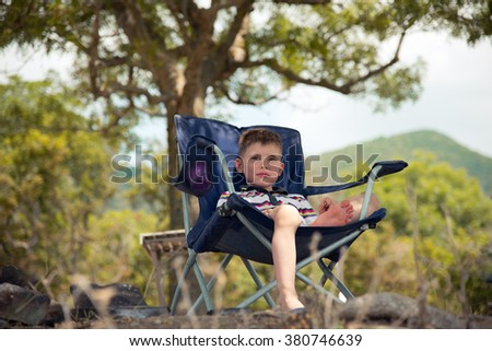 Child resting in a chair at the seaside - stock photo