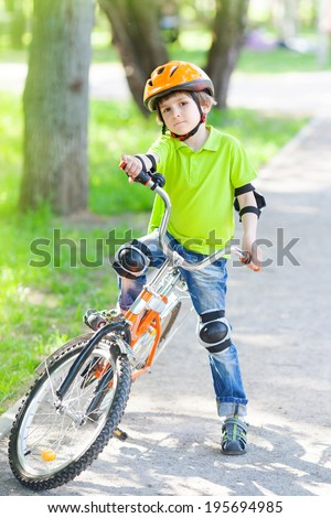 Child rides bike outdoors dressed in a colorful safety helmet  - stock photo