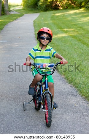 Child Riding His Bike on a Biking Trail in Summer - stock photo