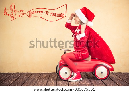 Child riding in red car. Kid holding Christmas bag. Xmas holiday concept - stock photo