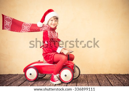 Child riding in red Christmas car. Xmas holiday concept - stock photo