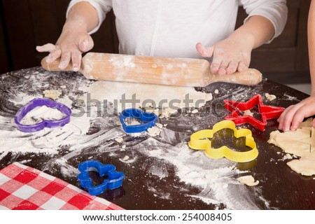 child rolls the dough for biscuits - stock photo