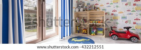 Child room for a boy with toys and wallpaper with cars - stock photo