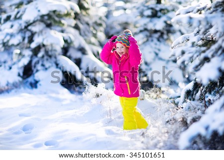Child running in snowy forest. Toddler kid playing outdoors. Kids play in snow. Christmas vacation in sunny winter park for family with young children. Little girl in colorful jacket and knitted hat. - stock photo