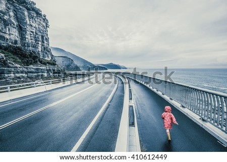 Child running on Sea Cliff Bridge, Grand Pacific Drive, Sydney, Australia. Image has vintage filter applied. - stock photo