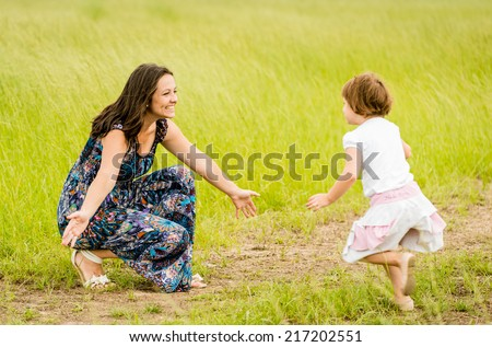 Child running to mother who is waiting with open arms - stock photo