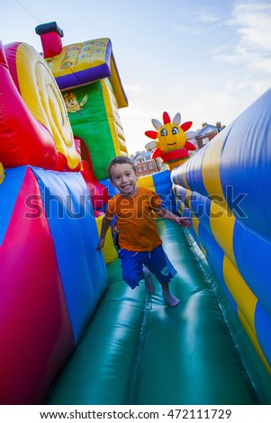 child runs on an inflatable trampoline. Blue sky.