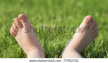 Child's bare feet on green grass in park
