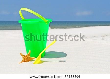 child's beach bucket by starfish at seashore - stock photo