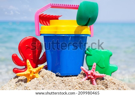 Child's bucket, spade and other toys on tropical beach  - stock photo