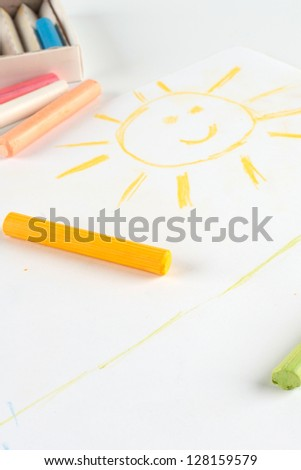 Child's drawing of a smiling sun. Done pastel on album sheet. - stock photo