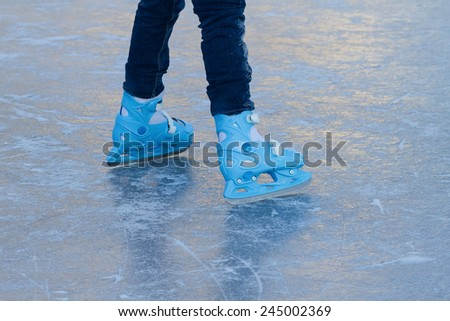 child's feet in blue skating on ice - stock photo