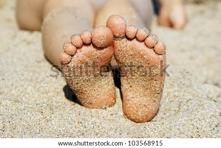 Child's feet in the sand close-up - stock photo