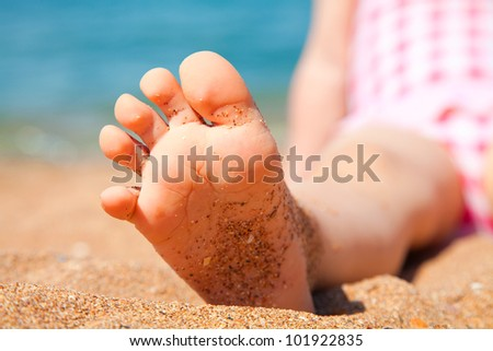 child's foot is close to the sandy beach of the seaside resort - stock photo