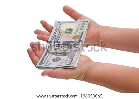 Child's hand and pile new cash U.S. dollars isolated on a white background