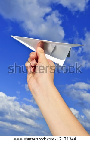 Child's hand holding a paper airplane on blue sky background - stock photo
