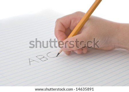 Child's hand holding a pencil, writing ABC alphabet on a white sheet of paper, over white background - stock photo