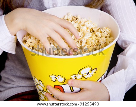 child's hand in a bucket of popcorn - stock photo