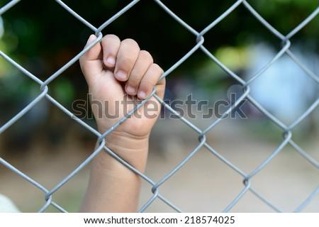 child's hand in jail.  - stock photo