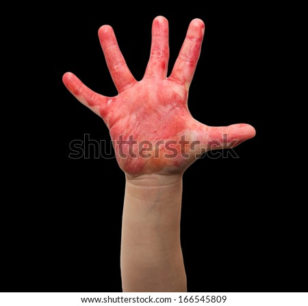 child's hand in red watercolor on a black background - stock photo