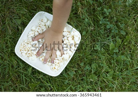 Child´s hand inside bowl of popcorn on green grass lawn outdoor - stock photo