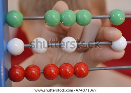 Child's hand moves beads on abacus