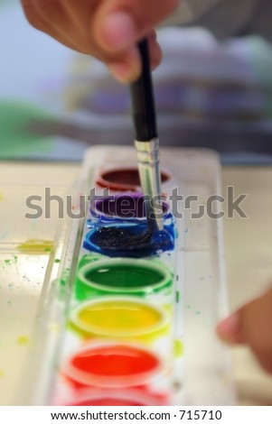 Child's Hand Painting A Watercolor Picture - stock photo