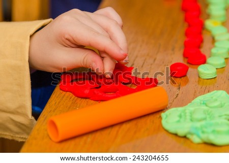 Child's hand playing with red and green play dough - stock photo