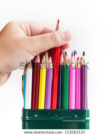 Child's hand pulls one pencil of the metal box - stock photo