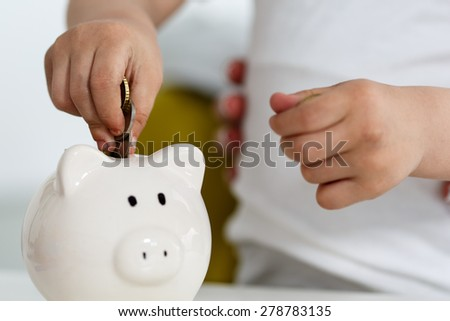 Child's hand putting pin money coins into white piggybank slot. Budgeting expenses concept. Making savings and effective investment concept. Future needs deposit
