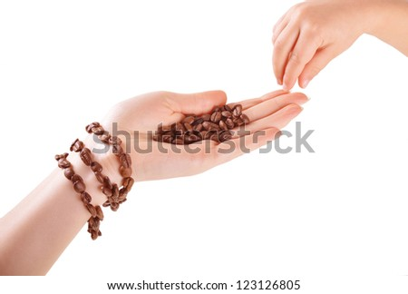 child's hand reaches for the coffee beans in a female hand with a coffee bracelet isolated on white background