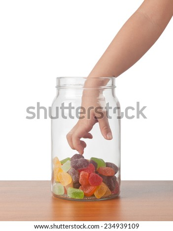 Child's hand reaching out to take candy from a jar  - stock photo