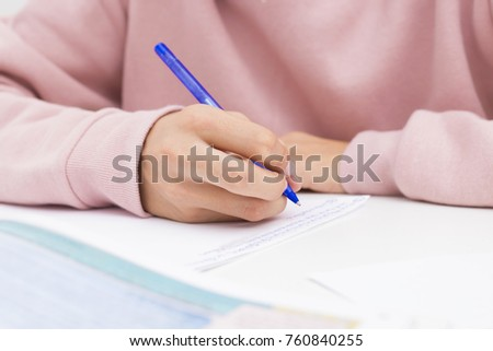 child's hand studying and writing on the school desk or home