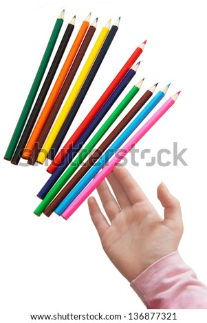 Child's hand throws color pencils. Isolation on white background. - stock photo
