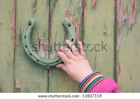 Child's hand using a horse shoe door knocker on a green door. - stock photo