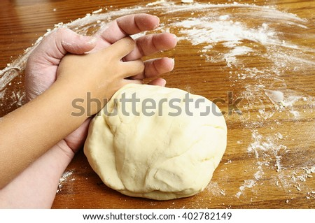 Child's hands and adult hand kneading bread dough on wooden table with flour  - stock photo