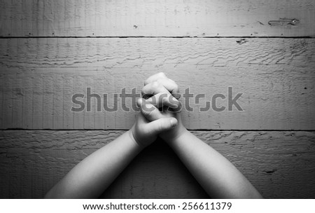 Child's hands folded together in prayer. Black and white photo - stock photo
