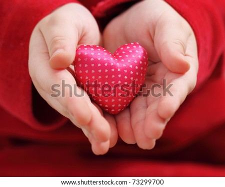 Child's hands hold heart from a pink satin with pattern