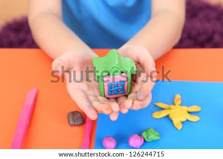 Child's hands holding hand-made plasticine house over desk - stock photo