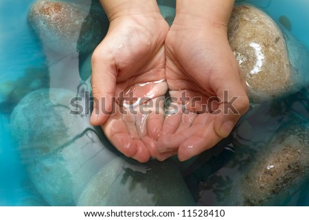 child's hands holding water, stones - stock photo