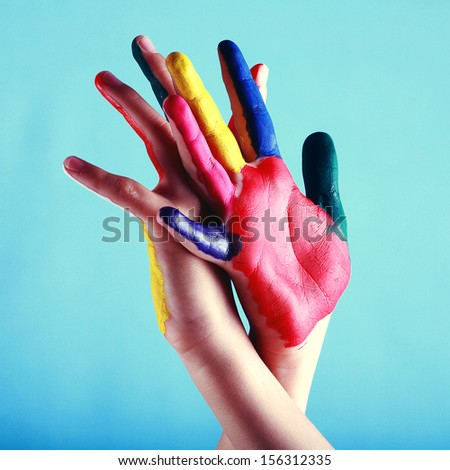 Child's hands painted with multicolored finger paints on blue background as a help concept - stock photo