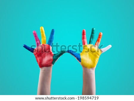 Child's hands painted with multicolored finger paints on green background - stock photo