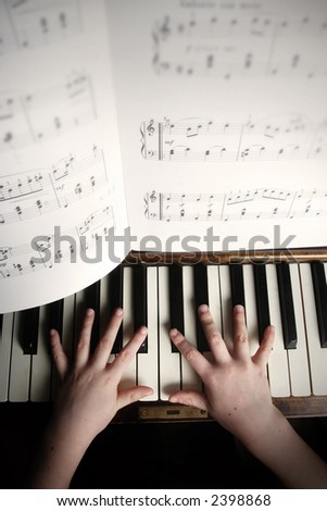 child's hands playing on a old piano - stock photo