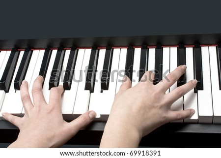 child's hands playing the piano - stock photo