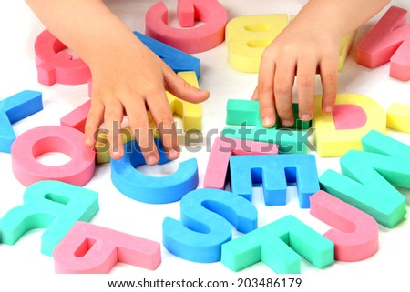 Child's hands playing with alphabet blocks - stock photo